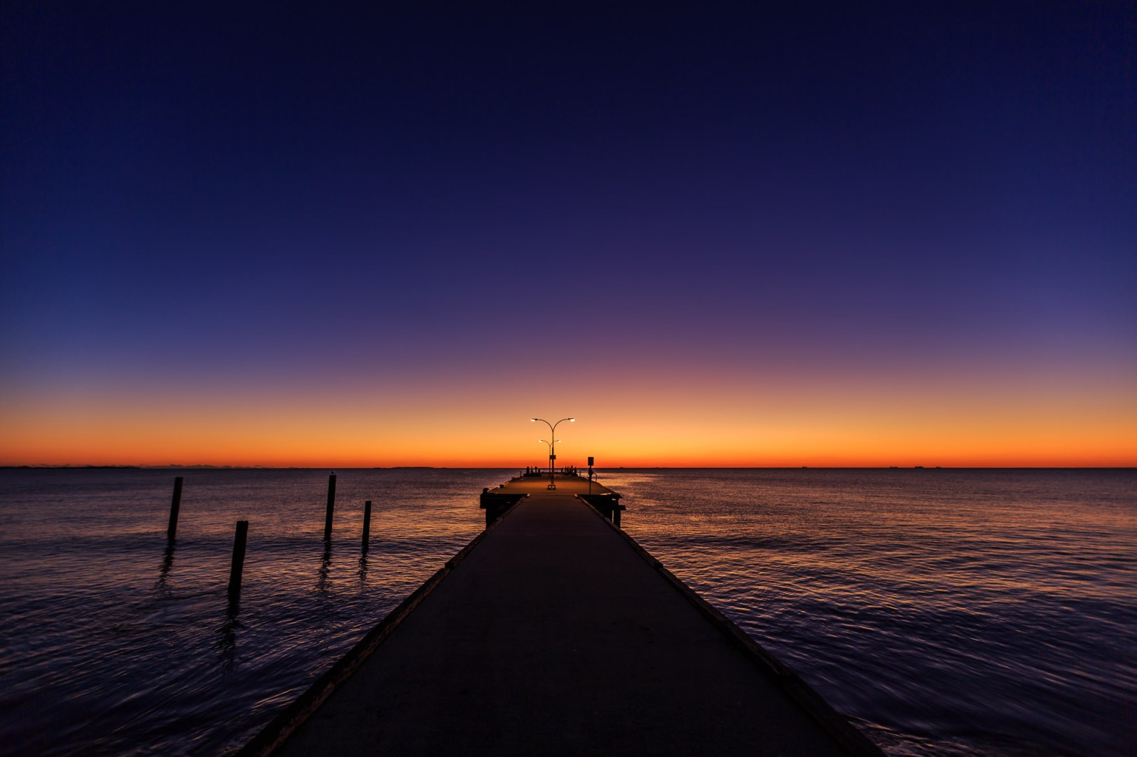 The sun sets during a clear winter day at Woodman Point Jetty, Western Australia.
